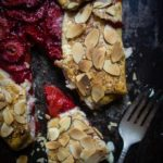 sliced strawberry almond galette with honey and fork