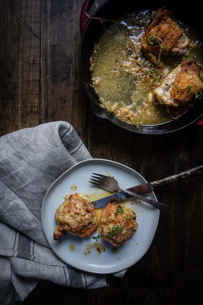 serving of chicken thighs in mustard sauce on a plate with skillet in background, chicken braised in white wine and dijon mustard