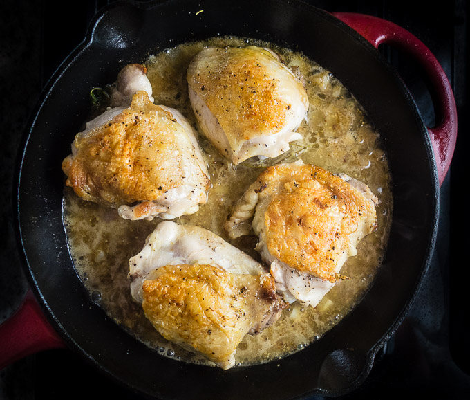 chicken thighs in cast iron skillet in white wine sauce