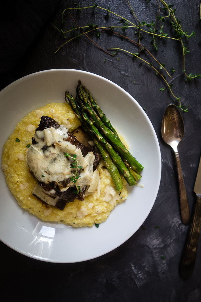 braised short rib on polenta with cream sauce and asparagus in pasta bowl