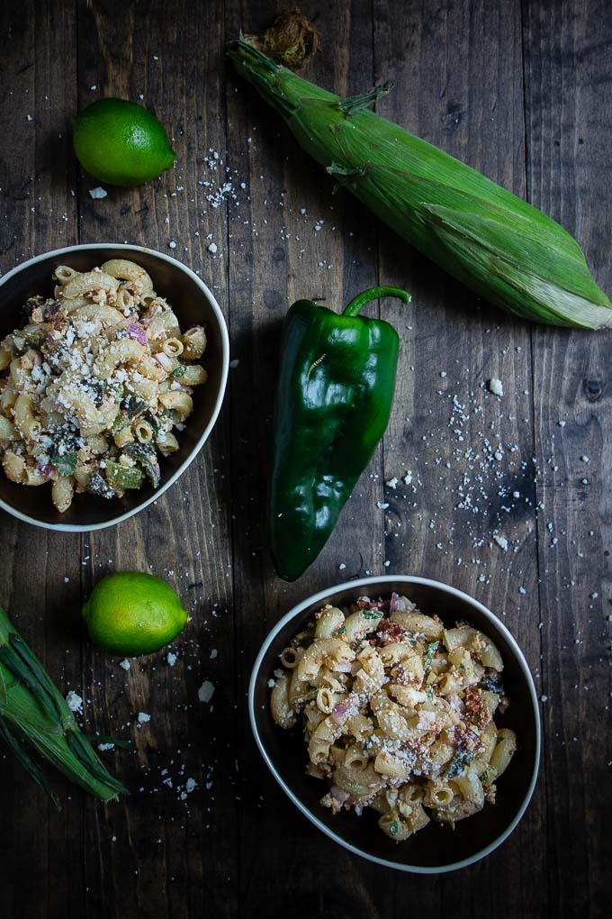 bowls of pasta with fresh corn and peppers and limes