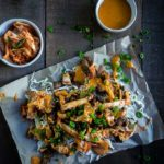 korean beef nachos with cheese sauce and kimchi