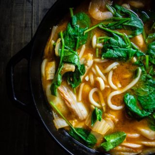 soup in a pot with noodles, spinach and thick broth