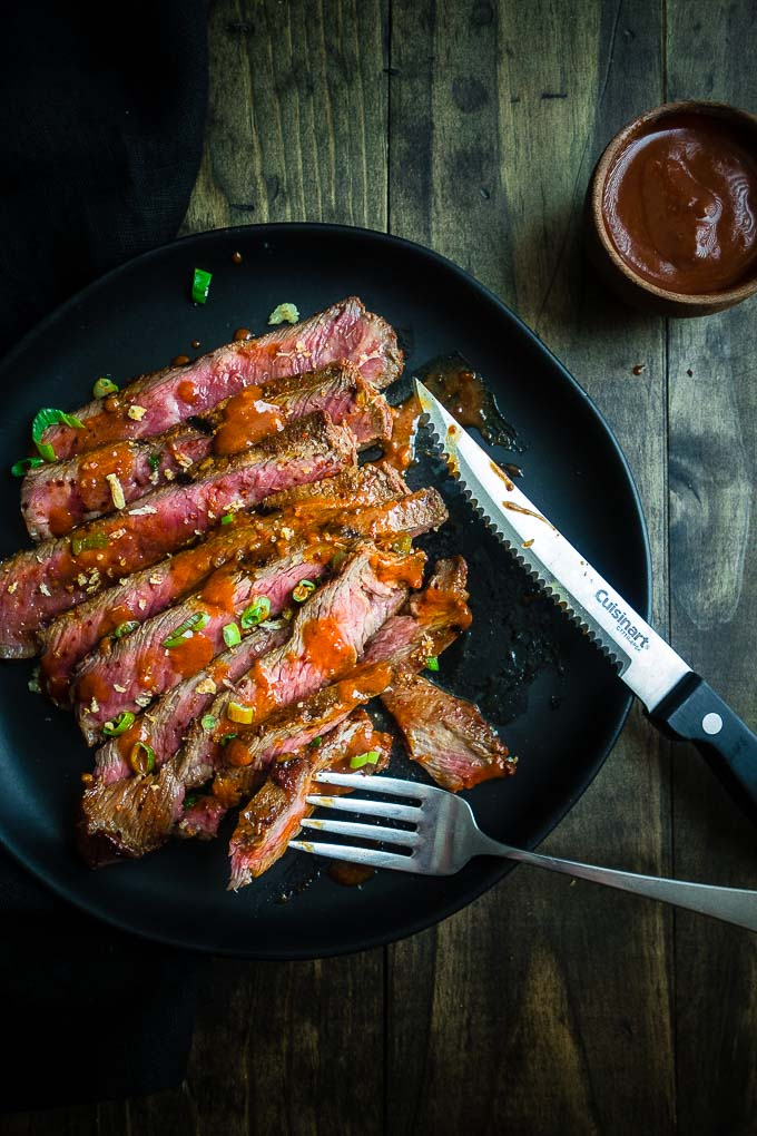 plate of sliced grilled beef with sauce and garnish