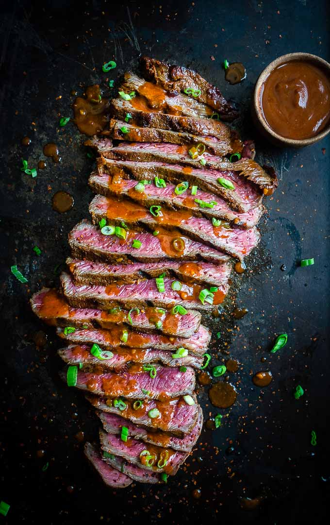 a sliced up flat iron steak with gochujang sauce