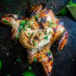 grilled cornish game hens covered in sauce and cilantro with lime