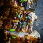 close up of ribs on a baking sheet with sauce and green onions
