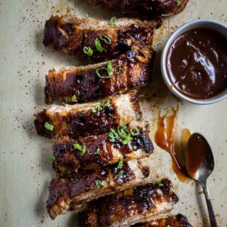 ribs on a cutting board with dish of sauce and spoon