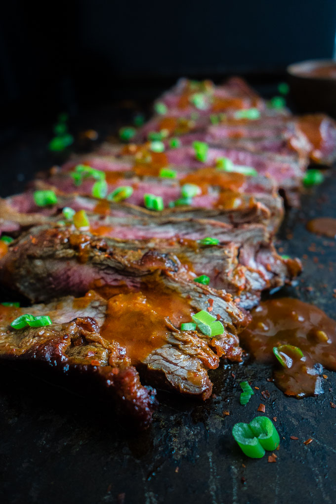 steak on a platter with sauce and green onions