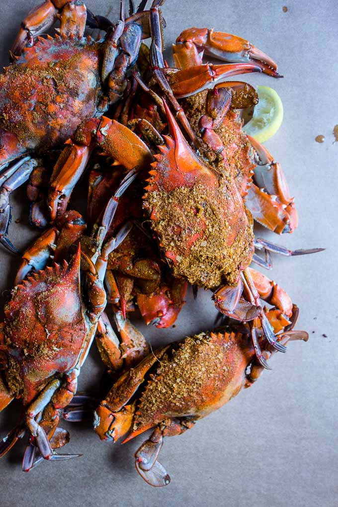 whole steamed blue crabs on a table with seasoning