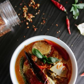 bowl of soup surrounded by chilies and spices