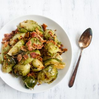 bacon braised brussels sprouts in a bowl with a spoon