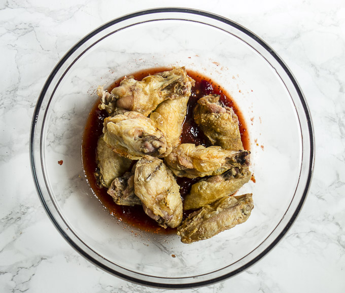 crispy chicken wing in bowl of sauce