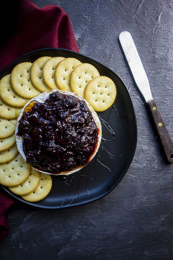 easy baked brie with cranberry chutney on a plate with crackers
