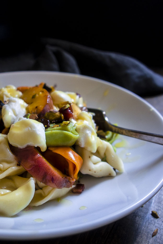 grilled peach tortellini salad in bowl with fork