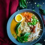 thai red curry ramen with fresh vegetables garnished with basil leaves and peanuts