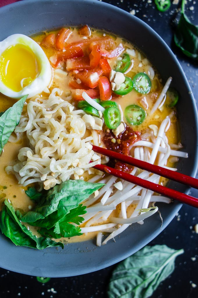 bowl of ramen noodles with red peppers, chilies, basil, egg and broth