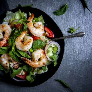 salad with shrimp on top in a bowl with chili dressing