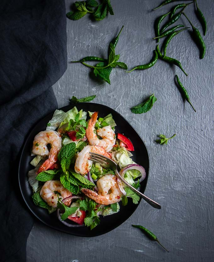thai shrimp salad on a plate with herbs and chilies