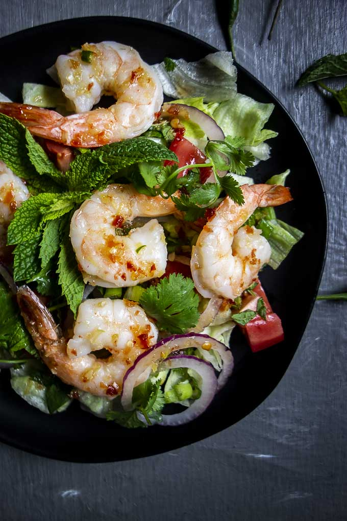 shrimp, greens, herbs, onions and red peppers in a bowl with chili dressing