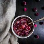 bowl of cranberry orange chutney with a spoon and fresh cranberries as garnish