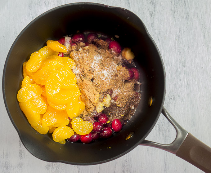 oranges, cranberries and sugar in a saucepan