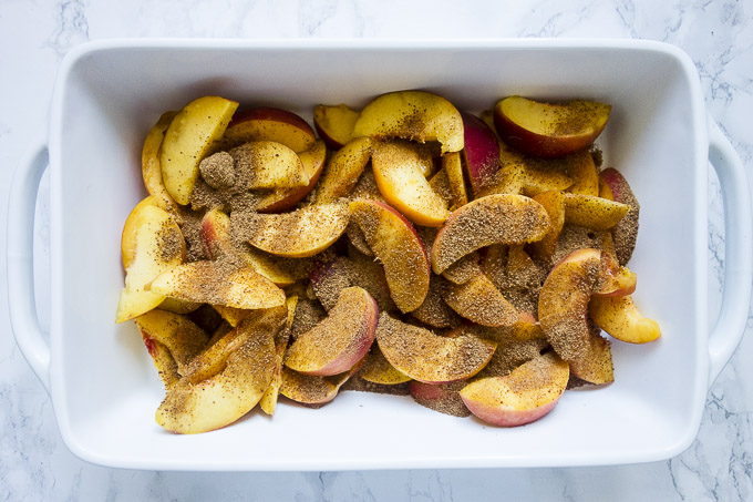 sliced peaches covered in coconut sugar in a baking dish
