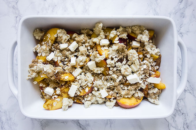 Sliced peaches, cookie crumble and butter in baking dish