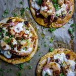 brazilian pizza on parchment paper with shrimp and parsley