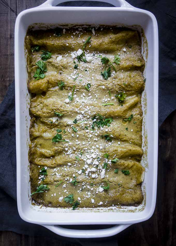 pulled pork enchiladas in a pan with cotija cheese and cilantro