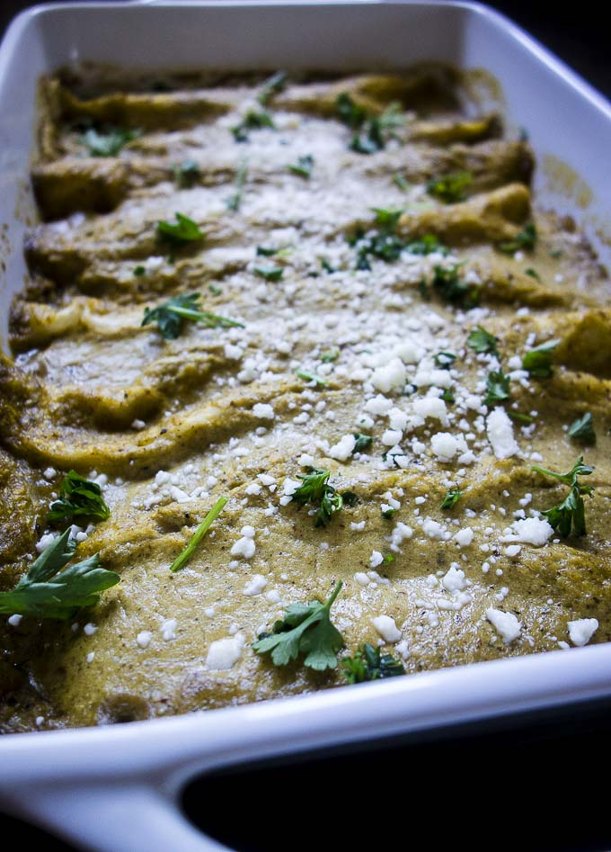 brazilian pulle pork enchiladas in a pan with garnishes