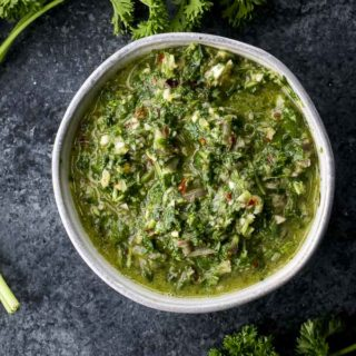 green herbs and sauce in a bowl garnished with parsley on the sides