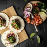 tacos on a platter with garnishes
