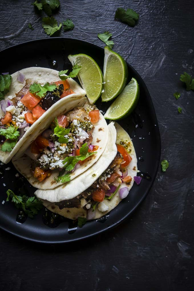 roasted pork belly tacos on a plate with cheese and cilantro