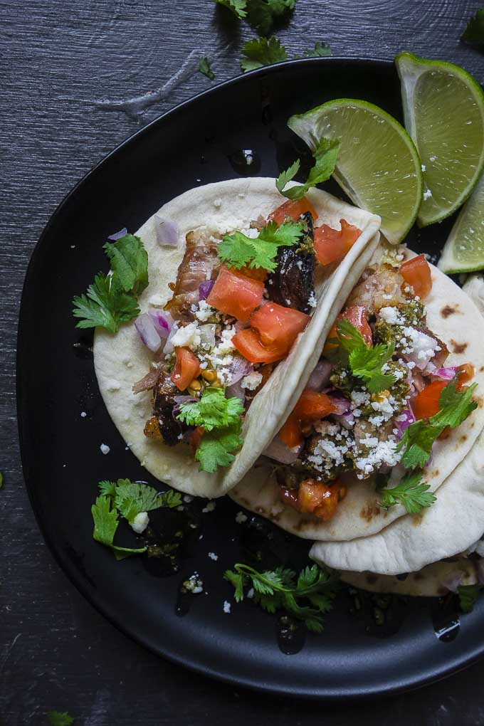 roasted pork belly tacos on a plate with lime and garnish