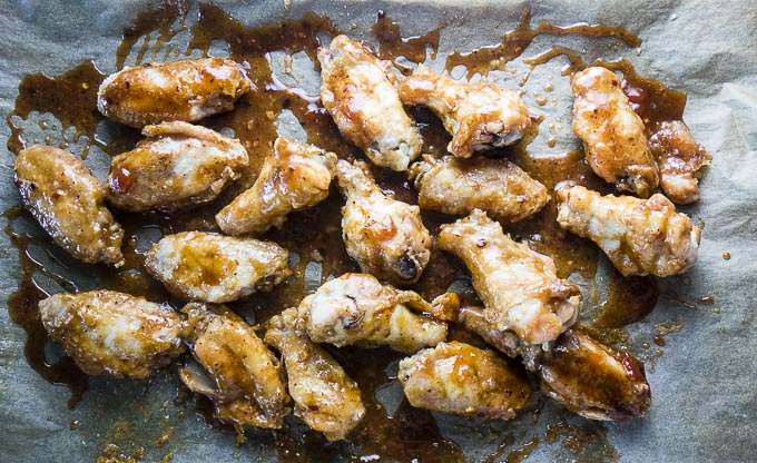 spicy guava chicken wings on a baking sheet with sauce