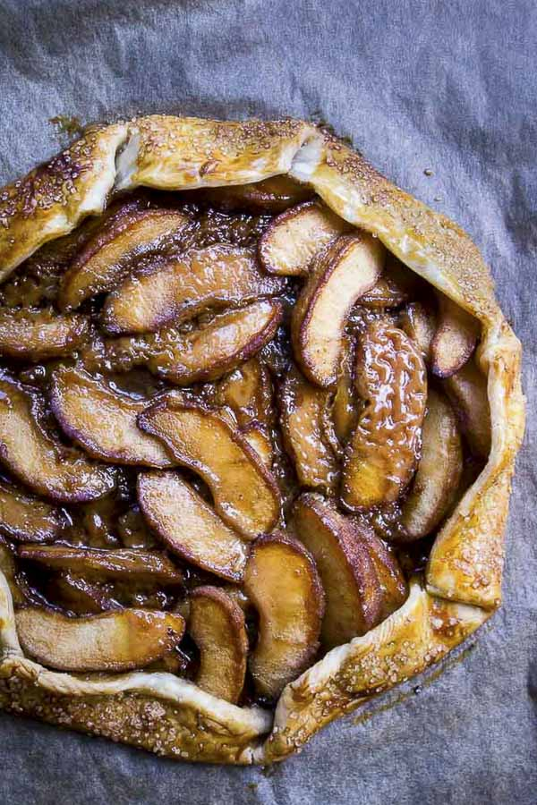 This easy Salted Caramel Apple Galette is made with sauteed apples, cinnamon, coconut sugar, a touch of nutmeg & salted caramel folded into a rustic galette and baked to a caramely goodness. This is the dessert you need in your life!apple galette | caramel apples | salted caramel apples | salted caramel apple pie | salted caramel apple  galette | cinnamon apple galette | thanksgiving pies | holiday desserts | easy apple desserts | how to make a galette