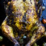 whole roasted moroccan chicken in a pan with olives and tomatoes