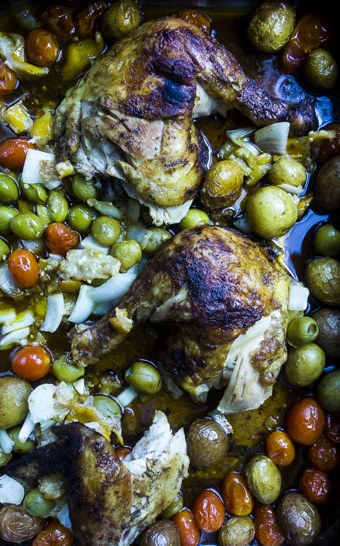 carved moroccan chicken in a pan with olives and tomatoes