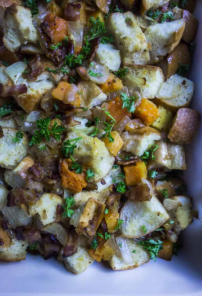 close up photo of baked butternut squash stuffing with bacon