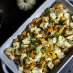 butternut squash stuffing with bacon in a baking dish garnished with mini pumpkins