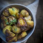 bowl of crispy roasted potatoes garnished with thyme