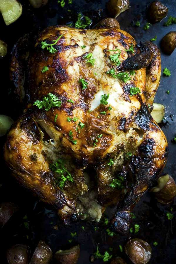 This Indian style roast chicken is marinated in ghee, yogurt, garam masala, honey, ginger and garlic and roasted to crisp, juicy perfection. Spiced roasted chicken is easy to make and are definite crowd pleaser. A whole roasted masala chicken is perfect for everyday meals, or awesome for a special holiday meal! Perfect roast chicken and potatoes! #chickendinner #chickencurry #chickenrecipes #masalachicken #indianchicken #roastchickendinner #roastedchicken