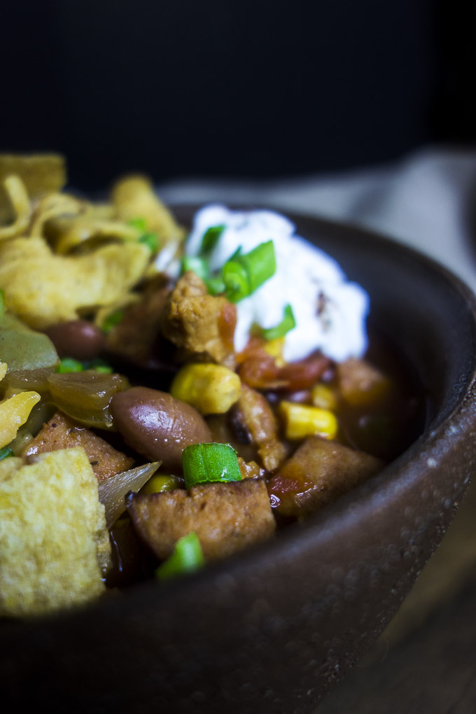 close up photo of instant pot turkey chili with green onions and sour cream in a bowl