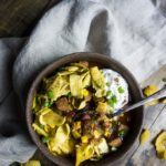 bowl of instant pot turkey chili with spoon and fritos, sour cream and green onions