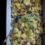 jambalaya stuffing in a baking dish with serving sppon