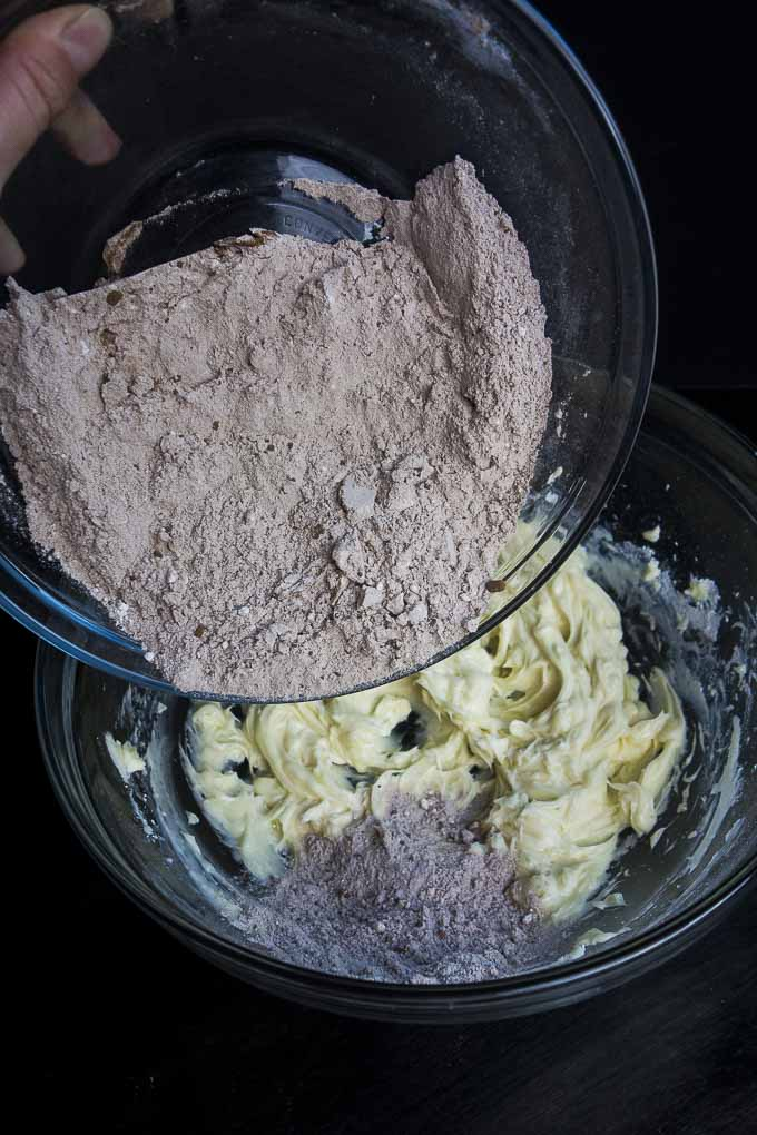 pouring flour into chocolate shortbread cookie batter