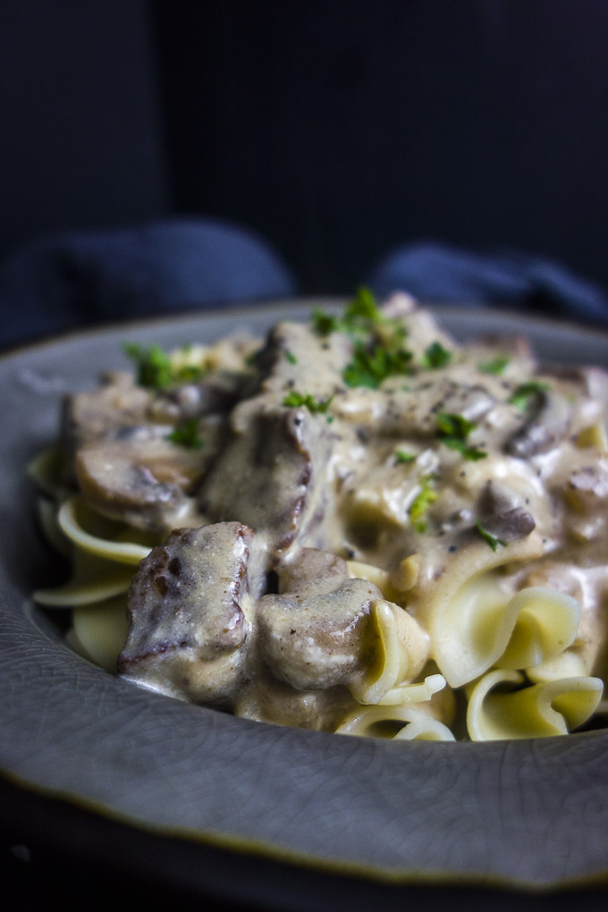 beef in a creamy sauce over egg noodles in a bowl