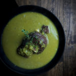 curried split pea soup in a bowl with ham hock