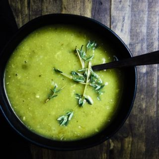 curried split pea soup in a bowl with thyme and a spoon